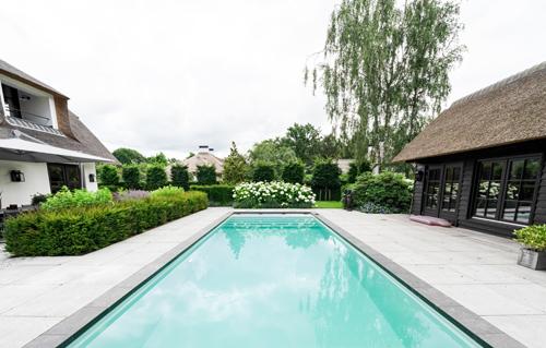 Zwembad omgeven door een ruim terras met grootformaat tegels van Schellevis beton